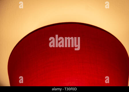 Abstract view of a red lampshade contrasting against a yelow ceiling - Stock Photo