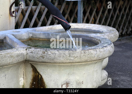 Details of a drinking fountain in Nyon, Switzerland. This fountain is made with light beige concrete and has old black pipe as a tab. - Stock Photo
