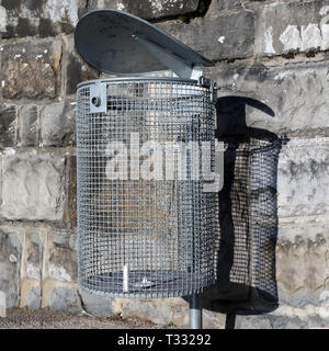Empty waste bin made of silver colored metal net. Photographed with grey stonewall. Photo was taken outdoors during a sunny day. - Stock Photo