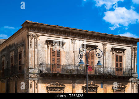 Typical traditional Sicilian architecture balcony, shutters and ornate stonework in Piazza San Giovanni in Ragusa Ibla, Sicily - Stock Photo