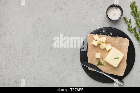 Chopped butter with rosemary in craft paper on wooden board over concrete background, top view. Homemade butter recipe mockup, copy space - Stock Photo