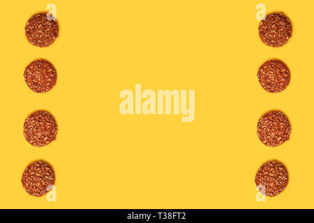 Tasty oatmeal cookies on a yellow background. - Stock Photo