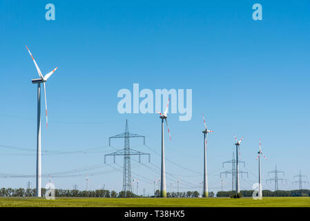 Wind energy plants and an overhead power line seen in Germany - Stock Photo