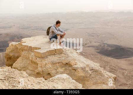 Mitzpe Ramon, Israel - 22 november, 2016: Man watching the horizon on the edge of Ramon crater cliff at  Negev desert, Israel - Stock Photo