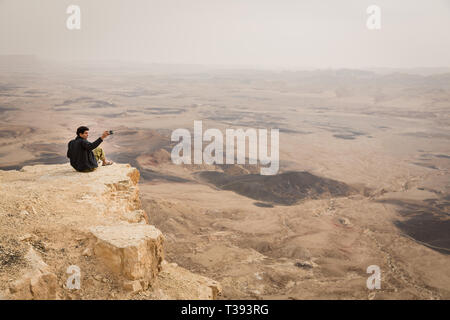 Mitzpe Ramon, Israel - 22 november, 2016: Man is taking a picture with a smartphone on the edge of Ramon crater cliff at  Negev desert, Israel - Stock Photo