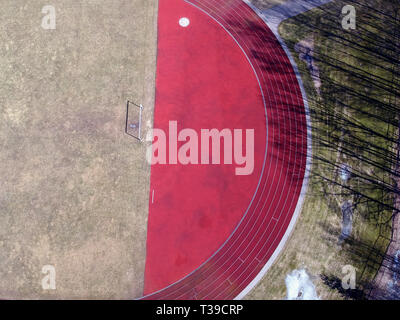 Empty spring time Football field and gate in stadium, aerial view - Stock Photo