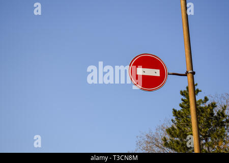 Road sign No entry against the blue sky and trees. - Stock Photo