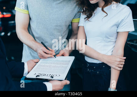 cropped view of car dealer holding clipboard while man signing contract near woman - Stock Photo