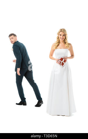 smiling pretty bride holding gift box, while tricky groom imitating running away isolated on white - Stock Photo