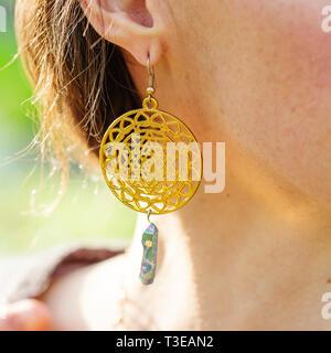 Sacred geometry golden earrings with crystal quartz on female ear - Stock Photo