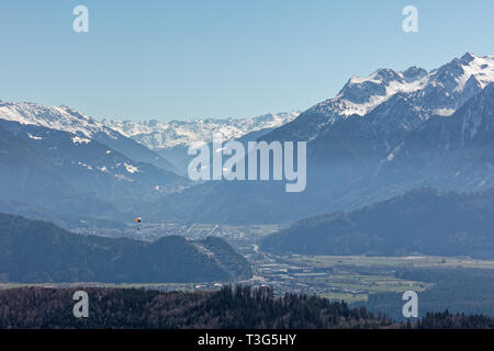Paraglider flying over Rhine valley with Silvretta massif in background - Dünserberg/Duenserberg, Vorarlberg, Austria - Stock Photo