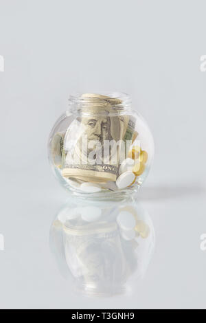 Pills and dollar bills in a glass bottle on a glass table. Medical or pharmacy prescription for health. Business, finance concept. Cost of the healthy - Stock Photo
