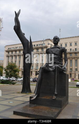 Hand and Broken Man bronze statue of 'Iuliu Maniu' in Revolution Square  Central Committee of the Communist party building behind, Bucharest Romania - Stock Photo