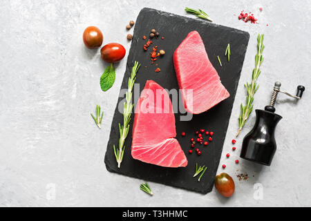 Raw fillet steak tuna with herbs and spices on gray background. Top view, flat lay - Stock Photo