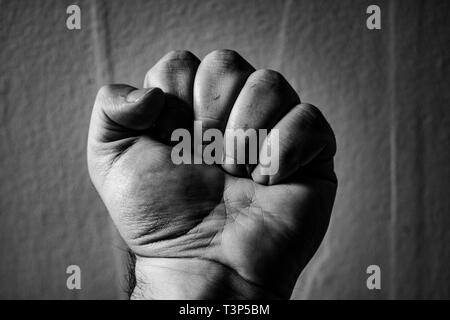 An aggressive monochrome adult male clenched fist isolated on a black background. - Stock Photo
