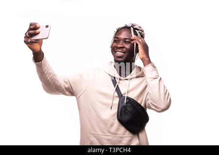 Close up of young beautiful dark-skinned man with afro hairstyle in casual smiling with teeth, holding smartphone, making selfie photo isolated on whi - Stock Photo