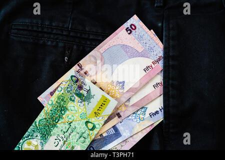 Qatari Riyal notes falling out of trouser or Pants Pockets - Stock Photo