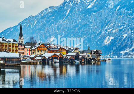 Historical quarters of Hallstatt with tall spire of Evangelical Church and wooden fishing boats' garages in port on Hallstattersee lake, Salzkammergut - Stock Photo