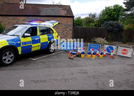Metroplolitan police car at display, with several traffic contol signs and blue light flashing - Stock Photo