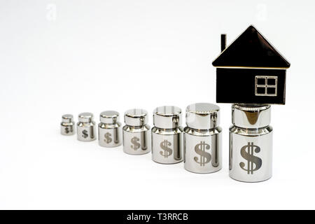 The house on the diagram of metal weights with laser engraving of dollar symbols on a light gray background. - Stock Photo
