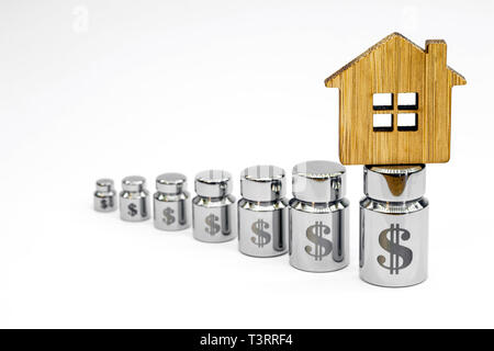 Wooden house made of bamboo on the diagram of metal weights with laser engraving of dollar symbols on a white background. Copy space. - Stock Photo
