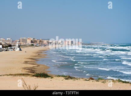 La Mata empty sandy beach coast surf in Mediterranean Sea, clear blue sky view from distance residential houses skyline, popular travel destinations,  - Stock Photo