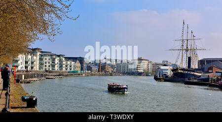 Bristol floating harbour quayside with modern apartment building on left, SS Great Britain on right and ferry going through docks - Stock Photo
