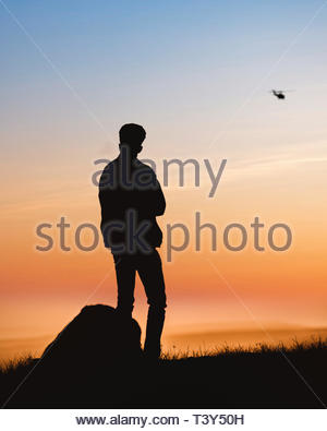 silhouette photography of man standing on grass - Stock Photo