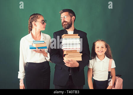 Back to school and home schooling. Literature lesson and reading grammar book. School time of sisters and father in library. Education in knowledge - Stock Photo