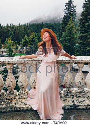 woman in pink dress leaning on beige concrete railing - Stock Photo