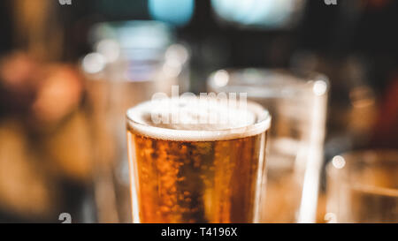 Close up of a pint of beer and empty glasses on a table - Stock Photo