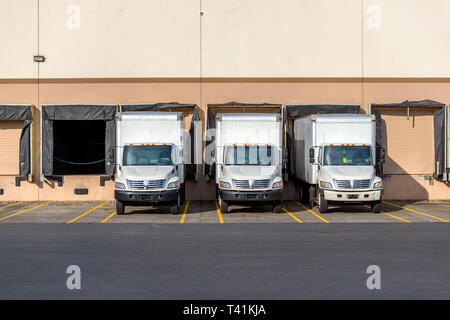 Small compact mobile rigs semi trucks with box trailers for local shipping and delivery standing in row at warehouse docks waiting for loading commerc - Stock Photo