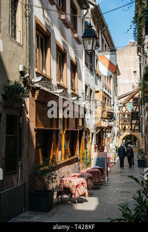 Strasbourg, France - Apr 19, 2016: Senior couple on cute street tiny vintage timbered houses buildings in central Strasbourg with Le Clou traditional winstub on 3 Rue du Chaudron - pedestrians - Stock Photo
