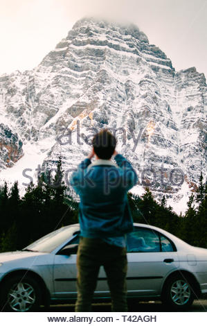 man standing near gray sedan taking picture of snow-covered mountain - Stock Photo