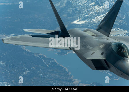 U.S. Air Force 1st Lt. Cory Clark, F-22 Demo Team safety observer, positions the Raptor for aerial refueling while en route to Travis Air Force Base for the Thunder Over the Bay air show March 25, 2019. 1st Lt. Clark received fuel along the way from a KC-10 Extender attached to the 9th Air Refueling Squadron out of Travis AFB. (U.S. Air Force photo by 2nd Lt. Samuel Eckholm) - Stock Photo