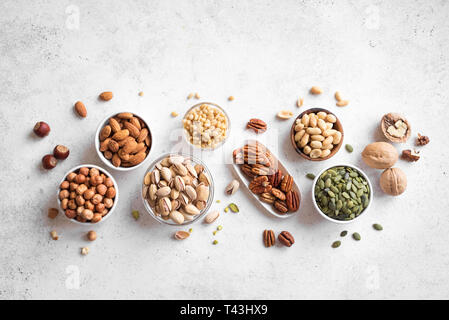 Various Nuts in  bowls on white background, top view, copy space. Nuts assortment - pecans, hazelnuts, walnuts, pistachios, almonds, pine nuts, peanut - Stock Photo