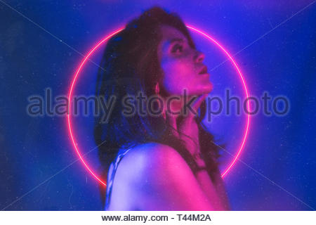 woman by pink neon circle - Stock Photo