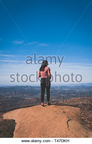 woman standing on rock - Stock Photo