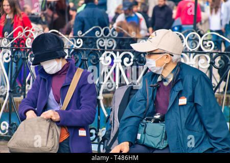 February 25, 2017 - Chefchaouen, Morocco: A couple of Asian tourists with their masks on, visiting Chefchaouen, in northern Morocco - Stock Photo