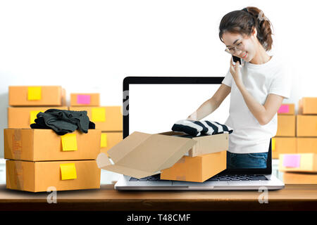 Young women get order product online and packing into box at her home. - Stock Photo