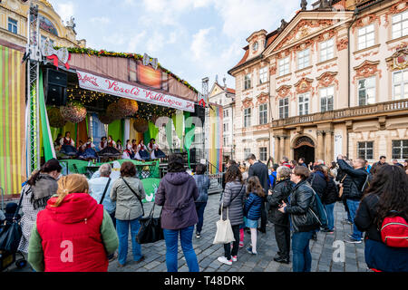 Crowds watch School children perform on stage during Pragues Easter Market celebrations in the Old Town Square - Stock Photo