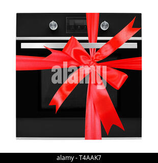 The electric oven gift tied red bow on a white background. It is isolated, the worker of paths is present. - Stock Photo