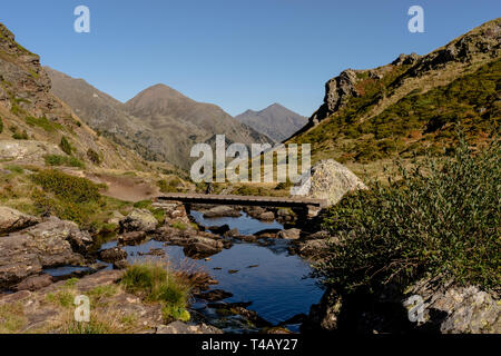 Wooden bridge in the hiking trail Estanys de Tristaina, Pyrenees, Andorra - Stock Photo