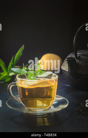 Cup of tea, melissa and black teapot on dark. Chinese tea concept. - Stock Photo
