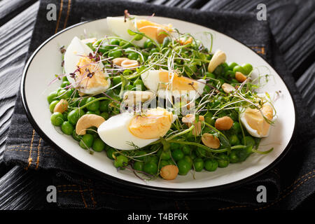 Green spring salad made from peas, micro greens, nuts and eggs close-up on a plate on the table. horizontal - Stock Photo
