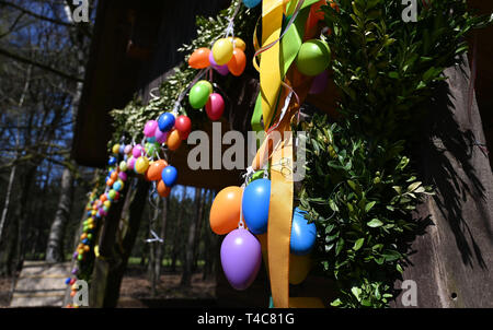 16 April 2019, Lower Saxony, Ostereistedt: Colourful Easter eggs hang at the house of 'Hanni Hase' in the forest near Ostereistedt. Here children from all over the world send letters to Hanni Hase at Easter, which are then answered at the post office in Zeven. Photo: Carmen Jaspersen/dpa - Stock Photo