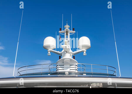 Communication antennas with navigation equipment, radar on the upper deck of the luxury white cruise ship.  There is a Thai flag with clear blue sky i - Stock Photo