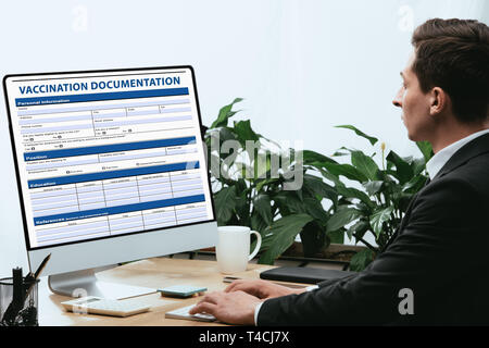 man in suit filling in Vaccination Documentation, Medical Concept - Stock Photo