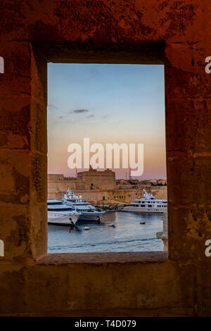 Luxury yachts in front of Fort St. Angelo at sunset, as seen from the guard tower window in Gardjola Gardens at Senglea, Malta - Stock Photo