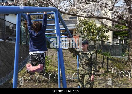 YOKOSUKA, Japan (Mar. 27, 2019) Culinary Specialist 3rd Class Maurissa Meza, from Merced, California, interacts with a child on the monkey bars during a community relations event at Yokosuka's Shunku Gakuen Orphanage. Ronald Reagan, the flagship of Carrier Strike Group 5, provides a combat-ready force that protects and defends the collective maritime interests of its allies and partners in the Indo-Asia-Pacific region. - Stock Photo